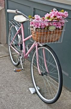 This vintage pink girls bicycle has beautiful pink flowers in a basket on the front of the bike   Set in a vertical format on a sidewalk  Stock Photo - 14260809