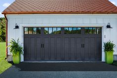 Clopay Coachman Collection carriage house garage door on a white farmhouse garage with gooseneck lights. Model shown: Design 13 with REC14 windows, painted black. www.clopaydoor.com