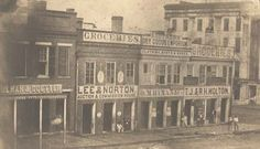 Businesses on the West side of Court Square, looking toward the southwestern corner of Montgomery Street and Court Square, in Montgomery, AL. From the ADAH Digital Archives : Item Viewer