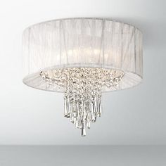 A sheer shade wraps around draping crystal in this flushmount ceiling light design.