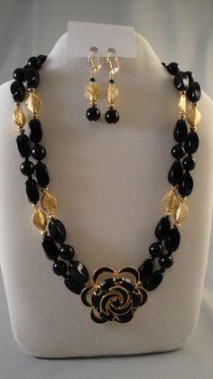 Este collar de 18 fue diseñada utilizando un alfiler vintage tonos de oro con esmalte negro y set de piedras negras. Ónix negro había trenzado abalorios ovalados y redondos y granos de oro entonado acento fueron agregados para una mirada elegante. El cierre es un cierre de color oro y oro