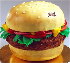 Tutorial with instructions on how to make a 3D sculpted hamburger or cheeseburger cake decorated in modeling chocolate and buttercream frosting by Wicked Goodies