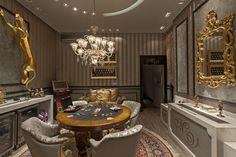 De estilo clássico e contemporâneo a Sala de Jogos dos arquitetos Maxwell Geraldi e Val Munhoz conta com detalhes que dão um toque suntuoso ao espaço como os rodapés de 15 cm sobrepostos e guarnições de 10 cm combinadas com rodameios na cor preta, da marca Santa Luzia, fornecidos e instalados pelo Ateliê Revestimentos. A atmosfera luxuosa é completada pelas esculturas de Leopardo, pelo piso vinílico Beaulieu cor Drifwood e pelas persianas Luxaflex e xales em gaze de linho cinza, também do…