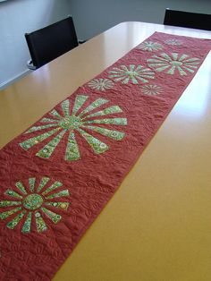 Pretty tablerunner. I think I would like to do it with snowflakes and a blue background.