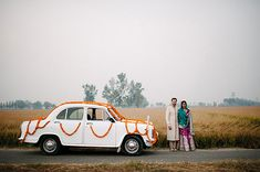 Portrait of a bride & groom next to their car.  LOVE the orange floral garland wrapped around the white car.   Photo by Celine Kim