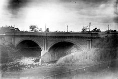 View of the High Street bridge across the Merri Creek, Clifton Hill, November 1892. Photograph taken by Thomas Beckett, probably from the railway embankment on the south side of Merri Creek.  Part of a collection of glass plate negatives taken by Dr Thomas George Beckett, doctor, pioneering radiologist and amateur photographer between 1891 and 1910. The collection is primarily of Beckett's family,  ...