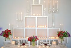 Main wedding table with a white backdrop cupboard with variety crystal and glass candle holders. Colourful tulips in glass and crystal vases.