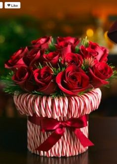 Stretch a rubber band around a cylindrical vase, then stick in candy canes around the vase Tie a red ribbon to hide the rubber band. Fill with flowers.
