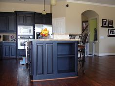 traditional kitchen with small wood top kitchen island with storage stainless steel appliances black iron chairs dark hardwood floors black painted kitchen cabinets of Tens of Inspiring Kitchen Islands with Storage and Chairs
