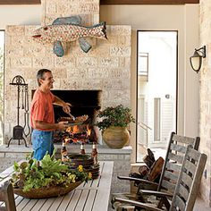 """John designed the fireplace on the outdoor porch with a functioning cooking rack inside the hearth. It's the ideal place for him to try out fiery new grilling recipes.  Source Guide Fireplace stone: handmade 5"""" x 11"""" White Wash Adobon bricks; claymex.com"""