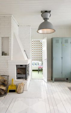 Love the painted brick walls, the fireplace, the painted white floorboards and the industrial cupboard and light. Doesn't look as harsh as it sounds. Very nice