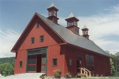 Red barn with three cupolas