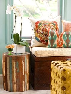 LOVE! Pale turquoise wall, windowseat, Ikat pillow, wood stool, orchid, yellow leather woven ottoman / coffee table