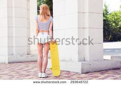 Rear view of a sexy young girl in shorts holding skateboard outdoors