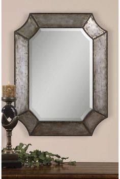 This unique decorative mirror features a hammered metal frame that gives it a rustic look. Hang it vertically or horizontally to fit the space. It looks lovely in a living room, hallway or bathroom.