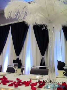 White feather centerpieces with black backdrop and accent of red