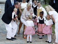 Fürst Albert + Fürstin Charlène: August 2015 Traditionell gekleidete Tänzer begrüßen das Fürstenpaar und die Zwillinge.