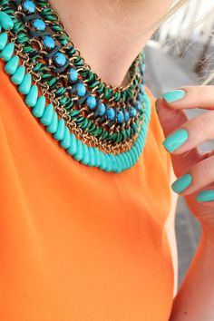 Turquoise necklace on orange blouse.  Love the color combination.