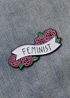 Feminist enamel pin with a quote on a banner surrounded by pink flowers