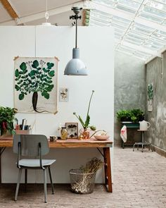 Nature-inspired painting hung above a desk in a greenhouse