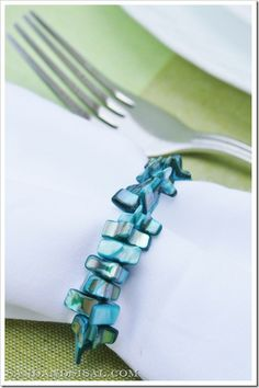 DIY blue coral napkin ring from Sand and Sisal blog: made with beads and 1mm clear stretch cording from Michaels