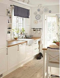 country kitchen style, I love the light feel and the wooden surfaces. I would change the blind above the sink to a more cheerful colour. But otherwise its scrumptious :)