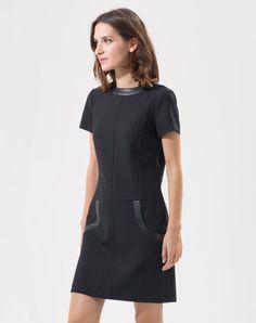 L'atout mode de cette robe noire compacte ? Sa ganse en simili cuir sur le col et les poches. On aime: - sa longueur idéale - ses poches arrondies - ses manches courtes  Longueur de la robe: 92 cm du haut de l'épaule jusqu'en bas pour la taille 38. Comptez un centimètre en plus par taille. Notre mannequin mesure 1m79 et porte une T.36.