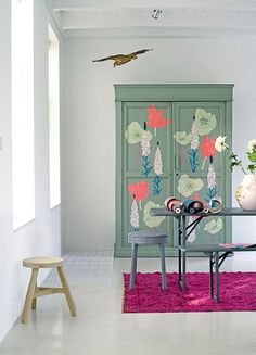 Floral patterns cut out of wallpaper and adhered to a cabinet.