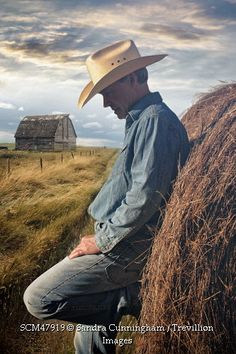 Trevillion Images - man-looking-down-and-leaning-against-bale-of-hay
