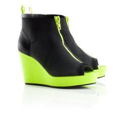 Shoes in wetsuit material with a peep toe and wedge heel. Patent details, decorative front zip and functional side zip. Rubber soles. $34.95