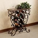 """Benedetto Wine Rack Table, TouchOfClass.com, $199.  Full of old world charm, the table top features an interesting crackle motif with an English walnut finish.  Metal base and scrolling accents are done in an aged bronze finish with copper and gold highlights. Wine rack measures 29""""Wx10""""Dx30""""H; approx. 20 lbs."""