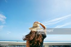 Stock Photo : Woman in sun hat admiring scenic view from balcony