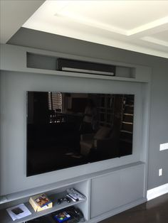 Curved Flat Panel Tv Mounted On A Wall With Sonos Playbar