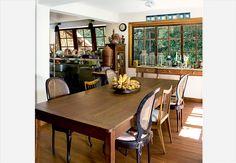 Aberta para a sala de jantar, a cozinha possui fogão e bancada de inox. Ao redor da mesa, cadeiras anos 1950 – algumas com encosto de palhinha – e outras peças garimpadas ao longo da vida do casal morador da casa. Projeto do arquiteto Alexandre Sodré