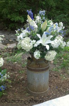 While white lilies, hydrangea, stock and blue delphinium seem more European than Prairie, that can be changed with a detail like using large metal milk jugs for the container. Example by Kistner's Flowers.