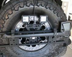 Possible: Vector Off Road EXO Rack.  I like the mounting position for axe/shovel/reverse lights/even more fuel if needed.  Would suck to take all that crap off to get to the spare though.