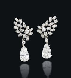 A PAIR OF DIAMOND EAR PENDANTS, BY CARTIER  Each stylised wing-shaped surmount composed of a cluster of brilliant, pear and marquise-cut diamonds, suspending a single detachable pear shaped diamond pendant, weighing approximately 4.22 and 4.02 carats respectively, with clips fittings, 4.2 cm, with French assay marks for platinum and gold Signed Cartier Paris, no. P9258