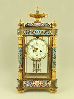 Antique 19th C Bronze Vincenti & Cie Champleve Cloisonne French Mantel Clock made of a bronze/ brass case of 4 columns ea. capped w' a flaming urn finial, covered w' a meticulously executed champlevé (French enameling that looks like cloisonné) in a floral pattern of pink/red/yellow+blue on a turquoise background. Crowning the clock is a wide floral champlevé & bronze urn atop a domed roof. All 4 sides of the clock are beveled clear glass, the front & back panels are hinged for access…