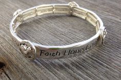 "The circles on this thin (approx. 3/8"") bracelet feature a heart, cross, fish, and anchor, representing faith, hope, and love.  I love the way this bracelet looks like it's a cuff but it stretches to easily fit over your hand.  Looks great stacked with other bracelets from our shop.  Visit our online shop for more Scripture based jewelry!"