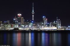 The shimmering Auckland skyline in New Zealand looks majestic against the backdrop of the ...