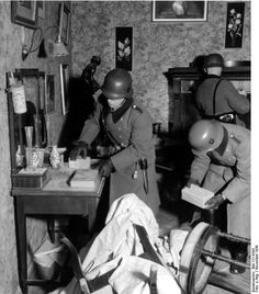 Warsaw, 1939 - German soldiers, (Nazis), searching for and removing anything of value in the abandoned homes of Jews. These Jews had been forcibly relocated to ghettos or were transported to concentration camps.