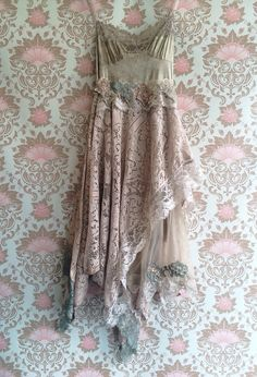One of a kind. The top of the dress has been hand dyed shades of sage, bronze and taupe with lace, applique and adjustable straps. The skirt