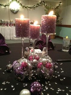 DIY Upside down wine glasses with small Christmas ornaments and garland in bottom and taped then hand glittered candles for on top. Beautiful and elegant centerpiece! Use anything in the bottom for other occasions!