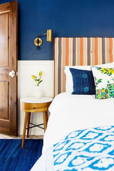 A colorful bedroom with a patterned headboard, tiny side table with small vase, and plush vibrant pillows