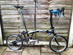 "Alasdair's Team Sky Brompton: ""It's an Alfine 11 hub and Sun rim, 25.8 drop bars for the Alfine drop leavers, with the bar bottom cut off, FSA hollow tech external ceramic bearings b&b, Dura Ace chain set with a 55t ring, Brompfication ti latches and levers, with XTR spd, Kojaks, long seatpin and a home made Sky team sticker set."" (found at LBC)"