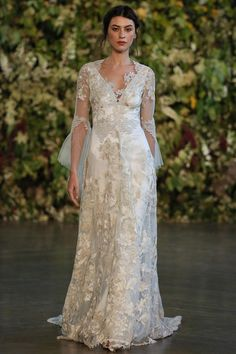 You are royalty in the MICHAELA wedding dress. This regal ensemble of gold and silver floral embroidered flowers has antique tulle long sleeves. Luxuriant Guipu