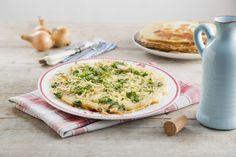 Pannenkoeken met gebakken uienringen, peterselie en kaas. Ga voor het recept naar de website van Koopmans: https://www.koopmans.com/recept/pannenkoeken-met-gebakken-uienringen-peterselie-en-kaas/