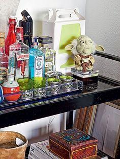 Com função de bar, o carrinho de chá do fotógrafo Lufe Gomes foi presente da designer Monica Cintra. As bebidas ficam ao lado de um boneco divertido do mestre Yoda, do filme Guerra nas Estrelas