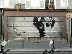 Sobre fachada de tienda, con una mujer y una mariposa, con tonos grises. Alejandro Estevez