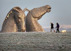 Stroll: Dog walkers pass the Kelpies in early morning sunshine on the Forth and Clyde canal near Falkirk, following heavy overnight frost